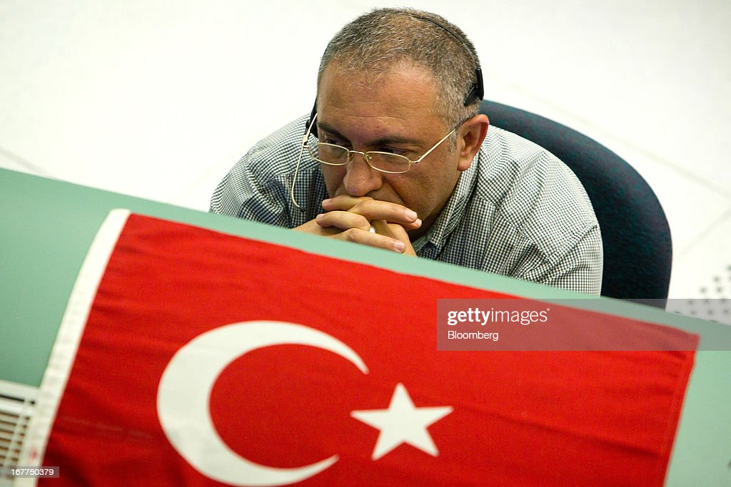 The Turkish national flag sits atop of a traders work station as he monitors financial information while working on the floor of the Borsa Istanbul, the stock exchange in Istanbul, Turkey, on Monday, April 29, 2013. Turkey is building a financial district in Istanbul and merged the 28-year-old Istanbul Stock Exchange with gold and derivatives exchanges into Borsa Istanbul this month. Photographer: Kerem Uzel/Bloomberg via Getty Images