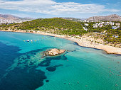 The turquoise waters of Kavouri Beach in Vouliagmeni, Athens, Greece, on a sunny summer day