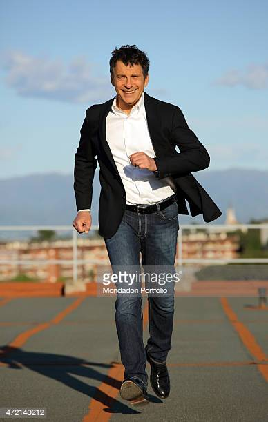'The TV host Fabrizio Frizzi pretending to run toward the camera in a photocall shooted outside the RAI TV studios where he presents the TV quiz...