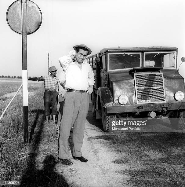 The tv presenter italian Enzo Tortora wearing a straw hat on a country road in front of a truck and a farmer strokes the nape of his neck looking...