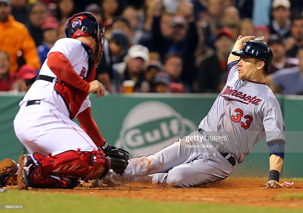 The Twins' Justin Morneau slides safely under the tag at home plate by Red Sox catcher David Ross in the sixth inning. The Boston Red Sox played the Minnesota Twins at Fenway Park on May 9, 2013.