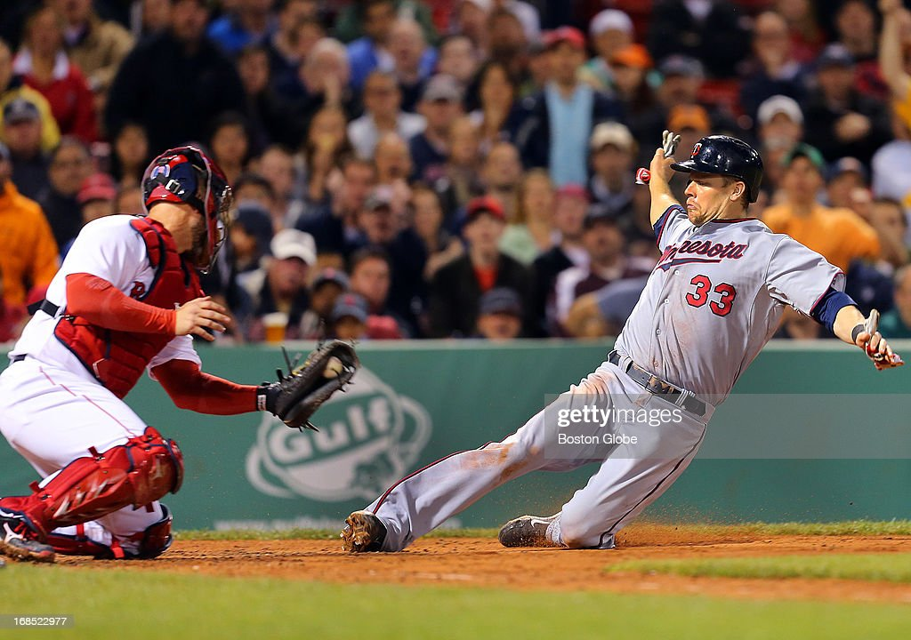 The Twins' Justin Morneau slides safely under the tag at home plate by Sox catcher David Ross in the sixth inning. The Boston Red Sox played the Minnesota Twins at Fenway Park on May 9, 2013.