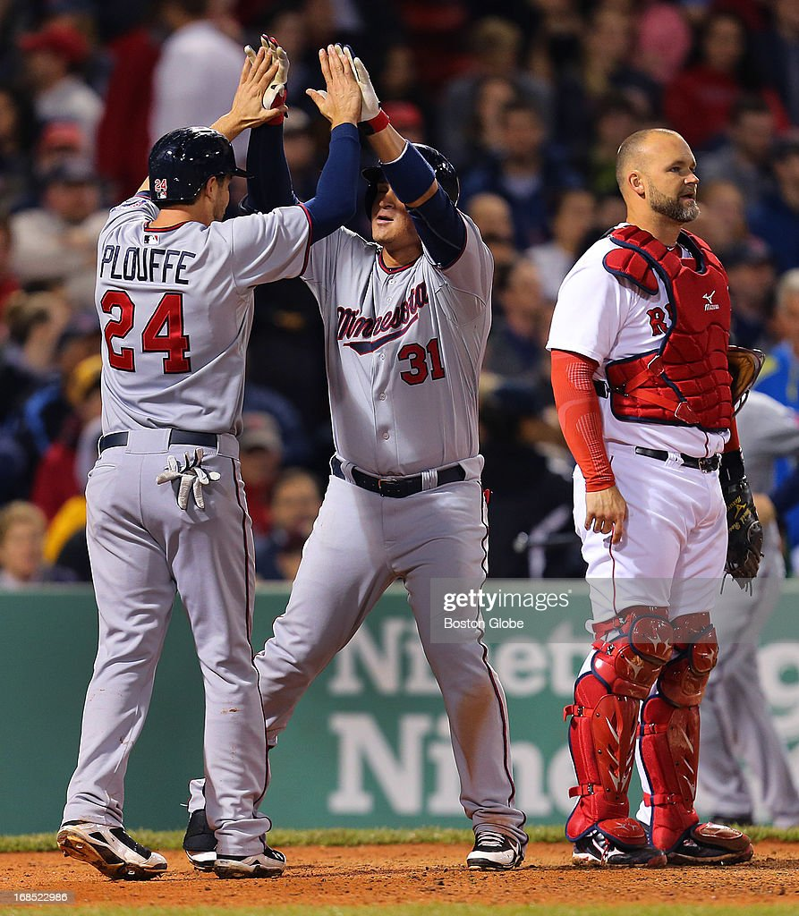 The Twins' Oswaldo Arcia, center, is congratulated by teammate Trevor Plouffe after his two-run home run in the sixth inning. Sox catcher David Ross looks away. The Boston Red Sox played the Minnesota Twins at Fenway Park on May 9, 2013.