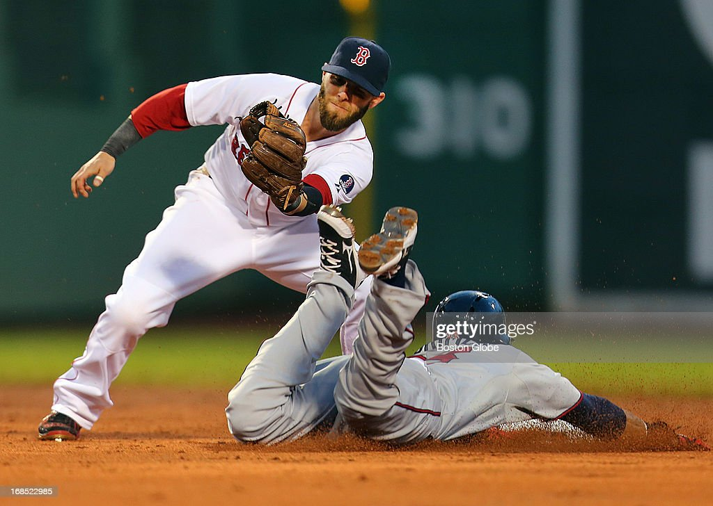 The Twins' Pedro Florimon slides in safely, beating Red Sox player Dustin Pedroia's tag for a third inning stolen base. The Boston Red Sox played the Minnesota Twins at Fenway Park on May 9, 2013.