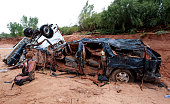 The twisted wreckage of two vans that were washed away in a flash flood with women and children inside rest on the bank of Short Creek on September...
