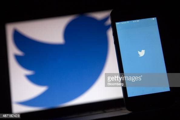 The Twitter Inc application and logo are displayed on a laptop computer and Apple Inc iPhone 5s in this arranged photograph in Washington DC US on...