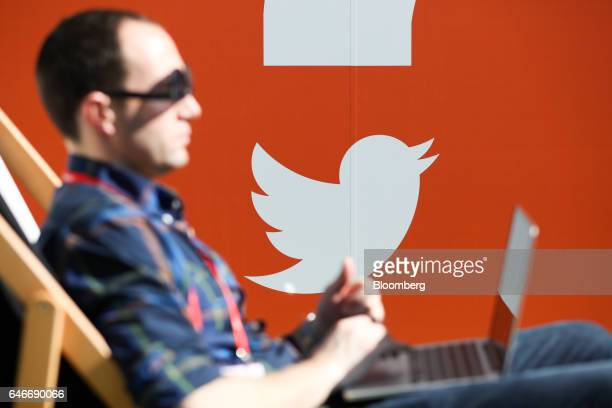 The Twitter Inc logo sits on a wall as an attendee sits on a deckchair using a laptop device on the third day of Mobile World Congress in Barcelona...