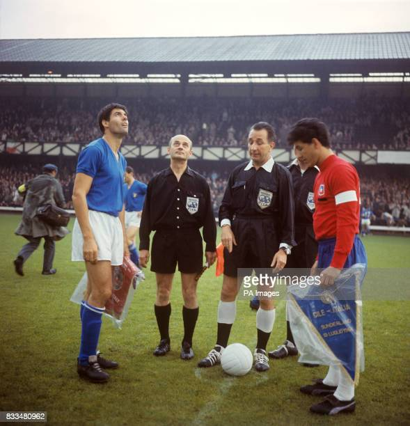 The two captains Italy's Sandro Salvadore and Chile's Leonel Sanchez flick a coin for kick off referee Gottfried Dienst looks on