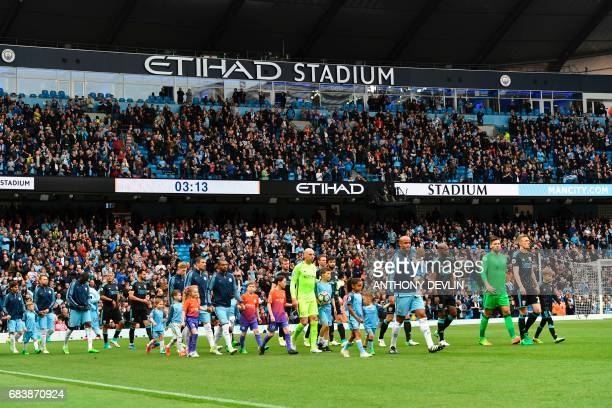 The two captains West Bromwich Albion's Scottish midfielder Darren Fletcher and Manchester City's Belgian defender Vincent Kompany lead out their...