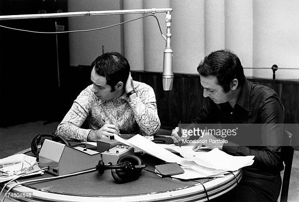 The two Italian radio broadcasters Renzo Arbore and Gianni Boncompagni sitting in the living recording studio decide on the schedule of the day the...
