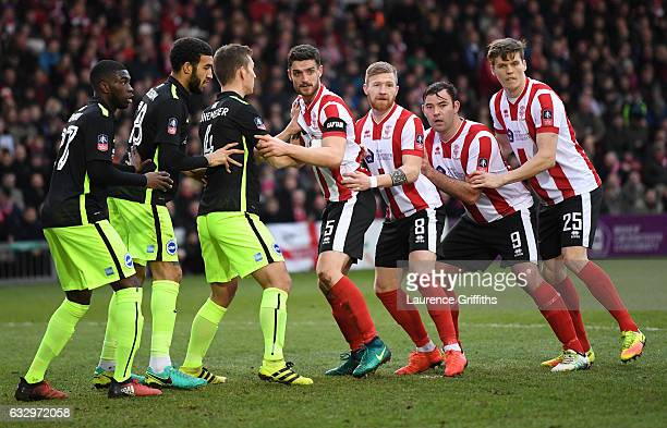 The two sides wait for an incoming corner during the Emirates FA Cup Fourth Round match between Lincoln City and Brighton and Hove Albion at Sincil...