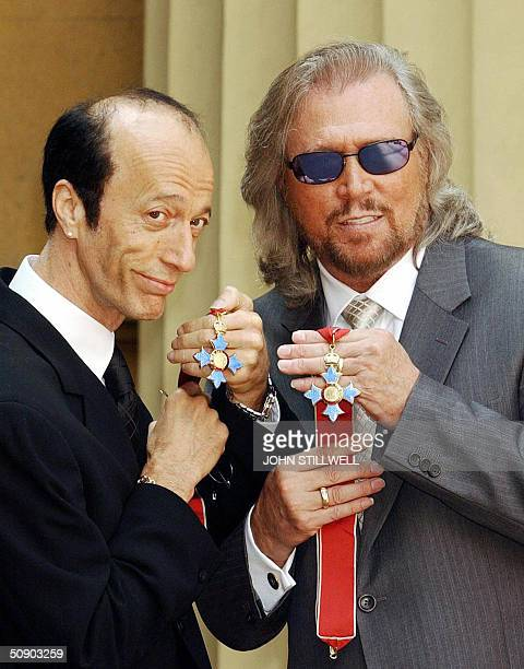 The two surviving members of the Bee Gees Robin and Barry Gibb hold their CBE's after receiving them from the Prince of Wales at Buckingham Palace...