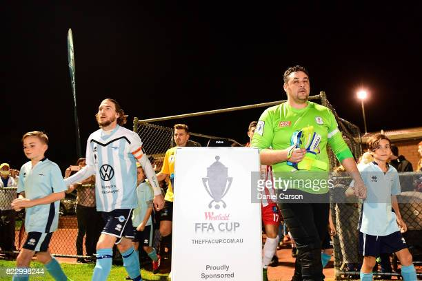 The two teams enter the arena lead by Angelo Konstantinou of Canberra Olympic FC and Daryl Platten of Sorrento FC during the FFA Cup round of 32...
