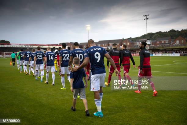 The two teams enter the field of play at the Wham Stadium home of Accrington Stanley during the Carabao Cup Second Round match between Accrington...