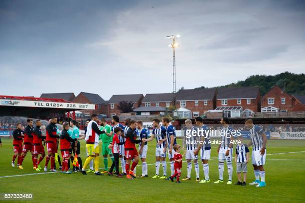 The two teams greet each other prior to of the Carabao Cup Second Round match between Accrington Stanley and West Bromwich Albion at Wham Stadium on...