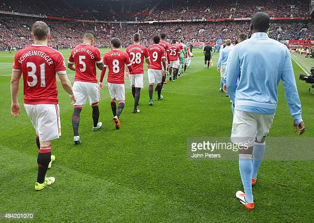 The two teams walk out ahead of the Barclays Premier League match between Manchester United and Manchester City at Old Trafford on October 25 2015 in...