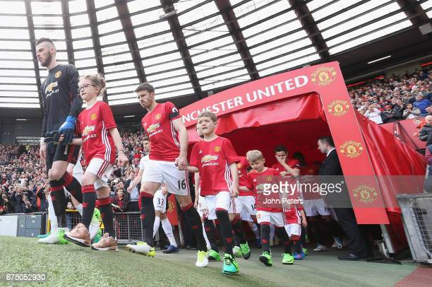 The two teams walk out ahead of the Premier League match between Manchester United and Swansea City at Old Trafford on April 30 2017 in Manchester...