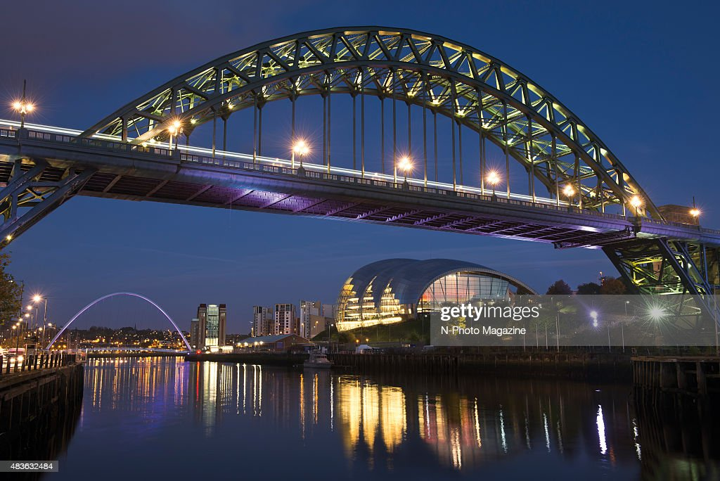 The Tyne Bridge over the River Tyne illuminated at night with the Gateshead Millennium Bridge visible in the background taken on October 18 2014
