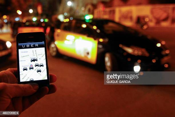 The Uber app is seen on a smartphone past cabs waiting for clients near the Sagrada Familia in Barcelona on December 9 2014 A judge on December 9...