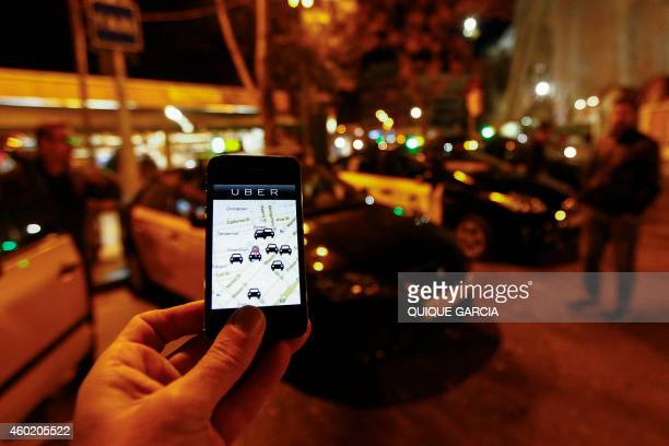 The Uber app is seen on a smartphone past cabs waiting fro clients near the Sagrada Familia in Barcelona on December 9 2014 A judge on December 9...