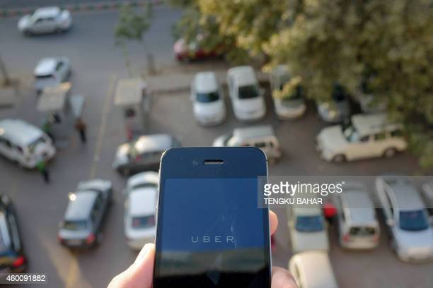 The Uber smartphone app used to book taxis using its service is pictured over a parking lot in the Indian capital New Delhi on December 7 2014 An...