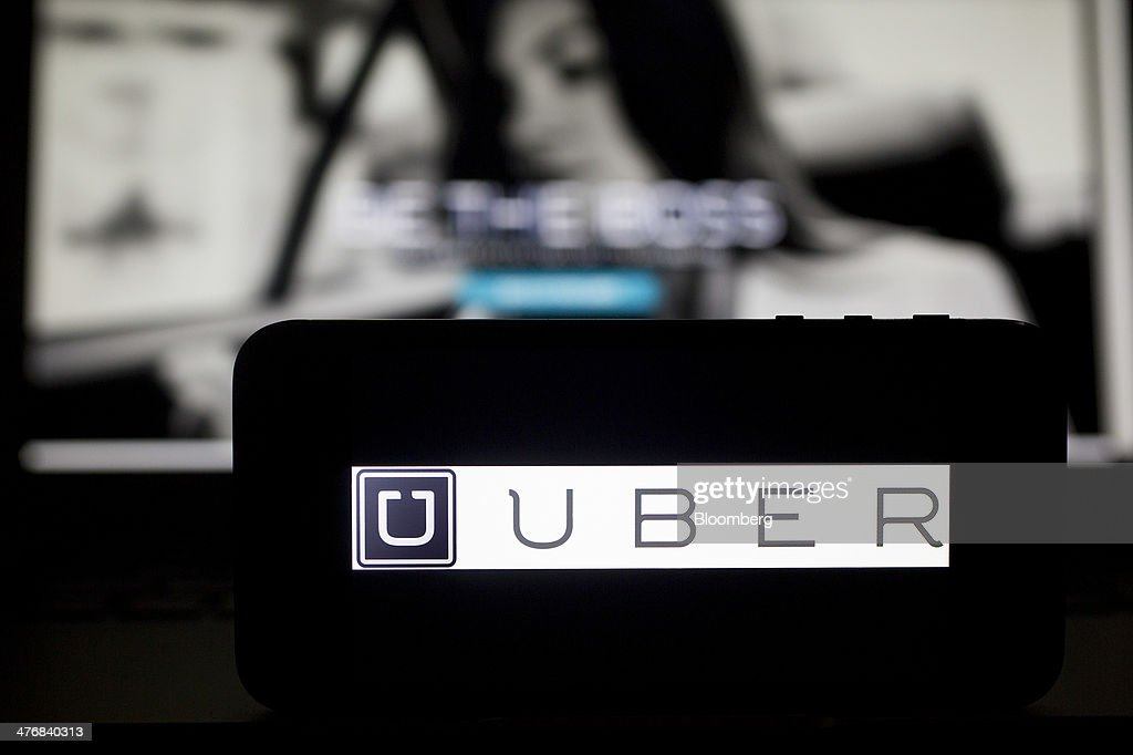 The Uber Technologies Inc. logo and website are displayed on an Apple Inc. iPhone 5s and laptop computer in this arranged photograph in Washington, D.C., U.S., on Wednesday, March 5, 2014. Uber, a startup that lets drivers pick up passengers with their personal cars and that was valued at $3.5 billion in a funding round last year, has raised $307 million from a group of backers that include Google Ventures, Google Inc.'s investment arm, and Jeff Bezos, the founder of Amazon. Photographer: Andrew Harrer/Bloomberg via Getty Images