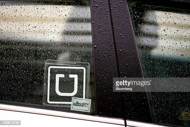 The Uber Technologies Inc logo is displayed on the window of a vehicle after dropping off a passenger at Ronald Reagan National Airport in Washington...