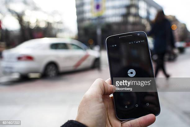 The Uber Technologies Inc ridehailing service smartphone app sits on a smartphone display in this arranged photograph at a taxi rank in Madrid Spain...
