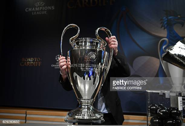 TOPSHOT The UEFA Champions League trophy is taken away after the draw for the round of 16 of the UEFA Champions League football tournament at the...