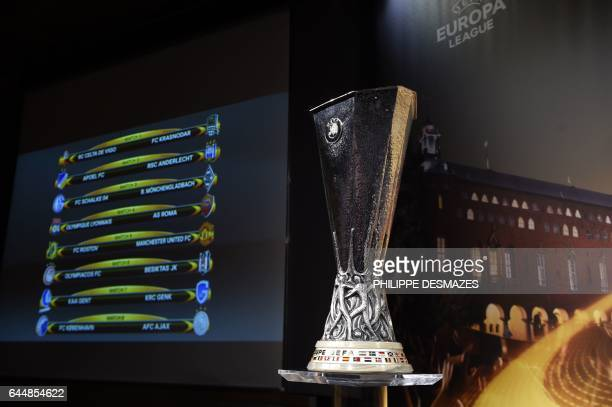 The UEFA Europa League trophy is displayed next to a screen showing the names of clubs that will be facing each other following the draw for the...