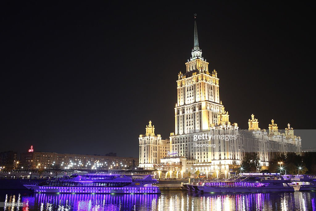 The Ukraine Radisson hotel stans illuminated at night near the River Moskva in Moscow, Russia, on Thursday, Oct. 10, 2013. Tinkoff Credit Systems Bank, operated by TCS Group Holding Plc, is valued at $2.5b to $3b for London IPO, which reflects P/E multiple of 9.5 to 11.4, Vedomosti reports, citing unidentified people familiar with offering documents. Photographer: Andrey Rudakov/Bloomberg via Getty Images