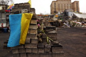 The Ukrainian flag is viewed on top of bricks used for barricades in Maidan Square the site of months of often violent protest that led to the ouster...