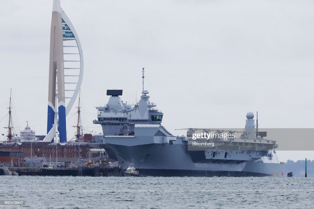 The U.K.'s Royal Navy new aircraft carrier, HMS Queen Elizabeth, sits docked at its home port in Portsmouth, U.K., on Wednesday, Aug. 16, 2017. The largely French-designed ship will carry 40 aircraft and about 700 crew members was built by a joint venture between BAE Systems Plc, Babcock International Group Plc and Thales SA. Photographer: Luke MacGregor/Bloomberg via Getty Images