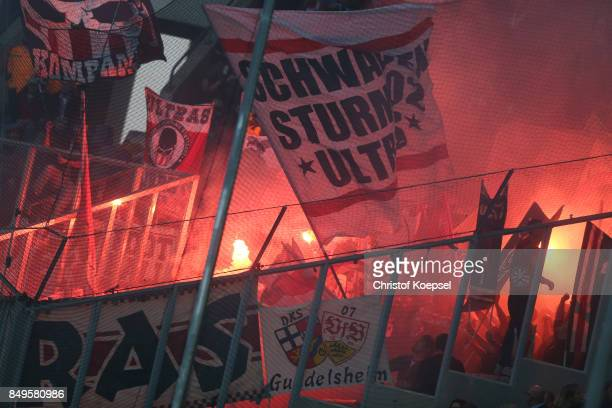 The Ultras supporters of stuttgart light flares and wave their flags during the Bundesliga match between Borussia Moenchengladbach and VfB Stuttgart...