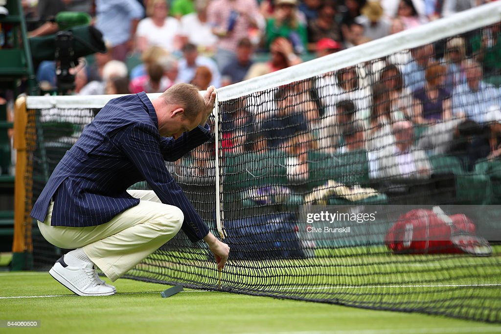 The Umpire adjusts the net on centre court on day five of the Wimbledon Lawn Tennis Championships at the All England Lawn Tennis and Croquet Club on July 1, 2016 in London, England.