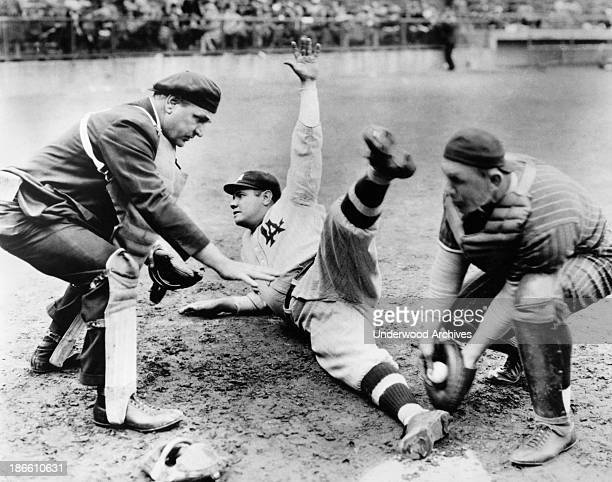 The umpire calls Babe Ruth 'Safe' as he slides into home plate on a baseball barnstorming tour mid 1920s