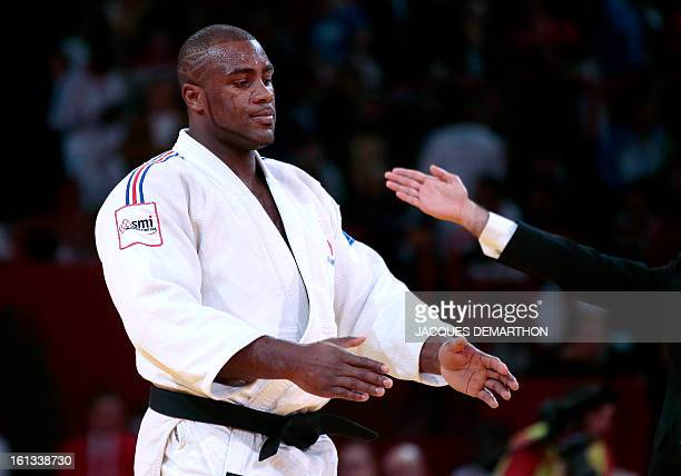 The umpire presents France's Teddy Riner winner over Cuba's Oscar Brayson on February 10 2013 in Paris during the semifinals of the Men 100kg of the...