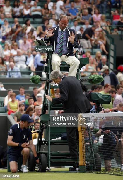 The umpire speaks with an official during the match between France's JoWilfried Tsonga and Austria's Jurgen Melzer during day one of the Wimbledon...