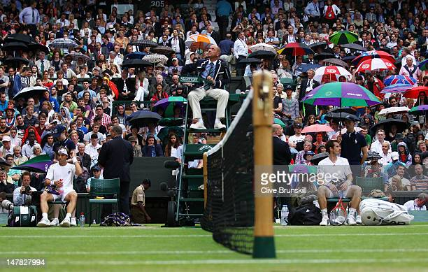 The Umpire suspends play as rain showers arrive as Andy Murray of Great Britain plays during his Gentlemen's Singles quarter final match against...