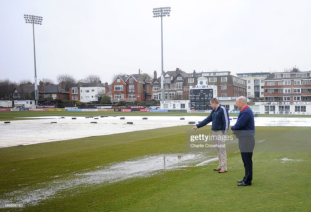 The umpires check the waterlogged pitch prior to the friendly match between Sussex and Loughborough MCCU at the Brighton and Hove Jobs County Ground on April 05, 2013 in Hove, England,