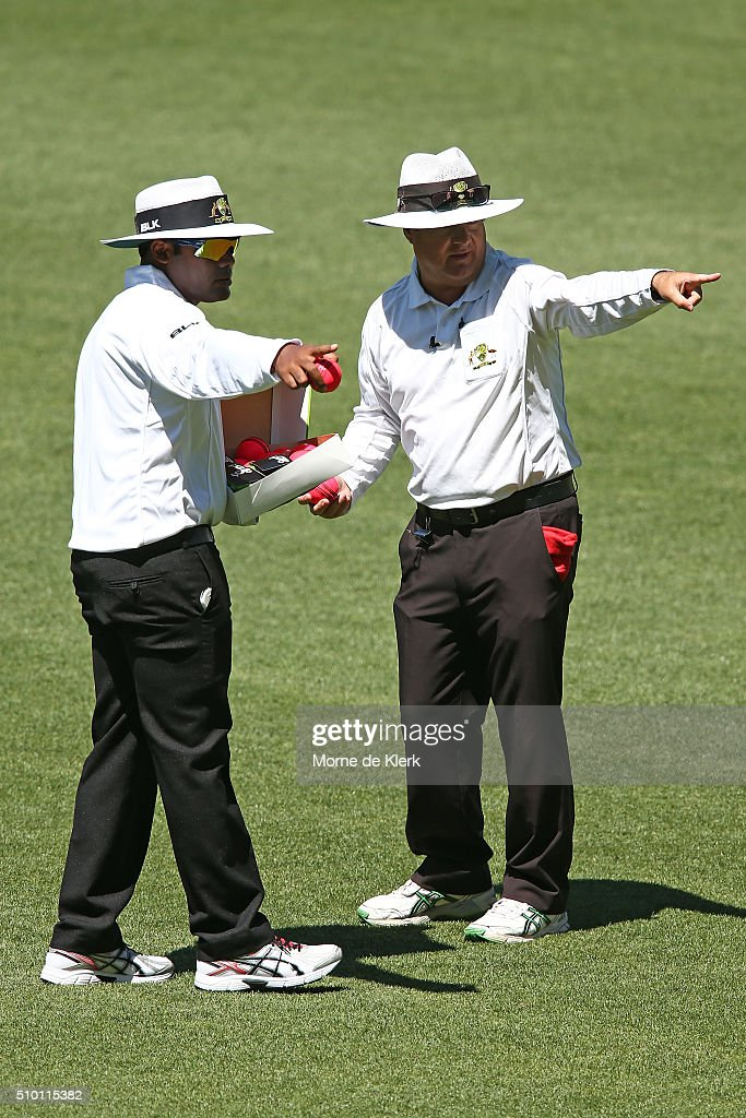 The umpires, Nitin Menon and John Ward discuss the state of the pink match ball during day one of the Sheffield Shield match between South Australia and Victoria at Adelaide Oval on February 14, 2016 in Adelaide, Australia.