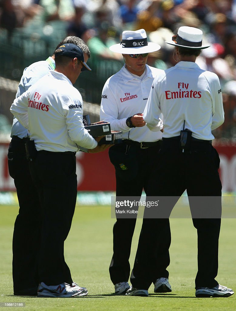 The umpires select a replacement ball after a six was hit in to new stand building site during day one of the 2nd Test match between Australia and South Africa at Adelaide Oval on November 22, 2012 in Adelaide, Australia.
