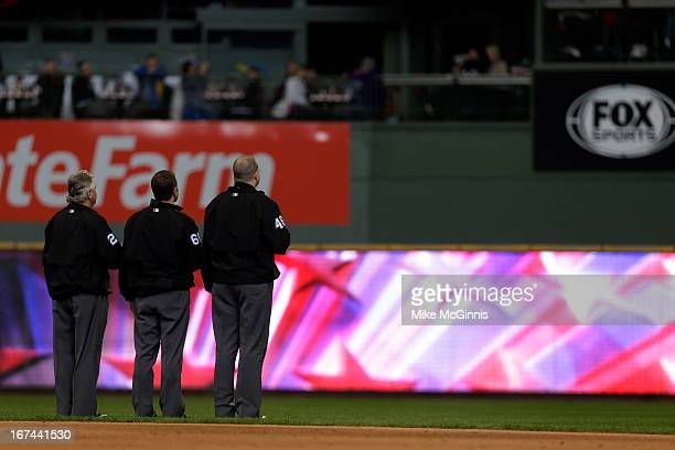The umpires stand for the playing of the star spangle banner during the game between the Milwaukee Brewers and the Chicago Cubs at Miller Park on...