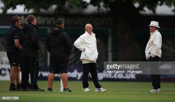 The umpires talk with the ground staff after stopping play for bad light during day one of the Tour match at New Road Worcester