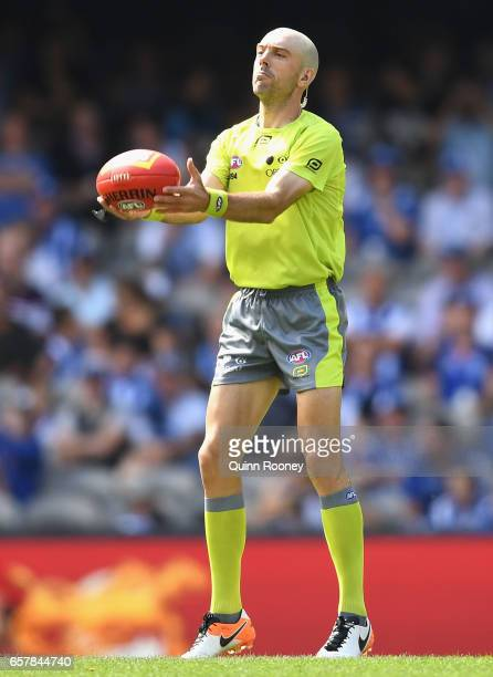 The umpires throw the ball up during the round one AFL match between the North Melbourne Kangaroos and the West Coast Eagles at Etihad Stadium on...
