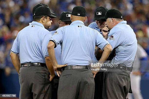 The umpiring crew discuss a call in the seventh inning as the Toronto Blue Jays takes on the Texas Rangers in game five of the American League...