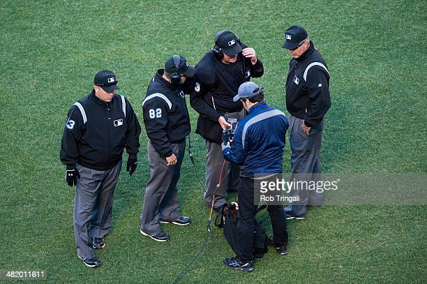 The Umpiring crew is seen huddled up taking a look at Instant Replay during the game between the New York Mets and the Washington Nationals at Citi...