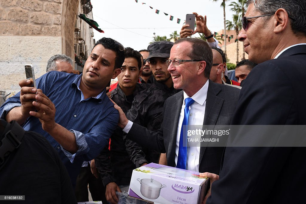 The UN envoy for Libya Martin Kobler poses for a picture with Libyans during a tour in the Tripoli's old city on April 5 2016 Kobler flew into...