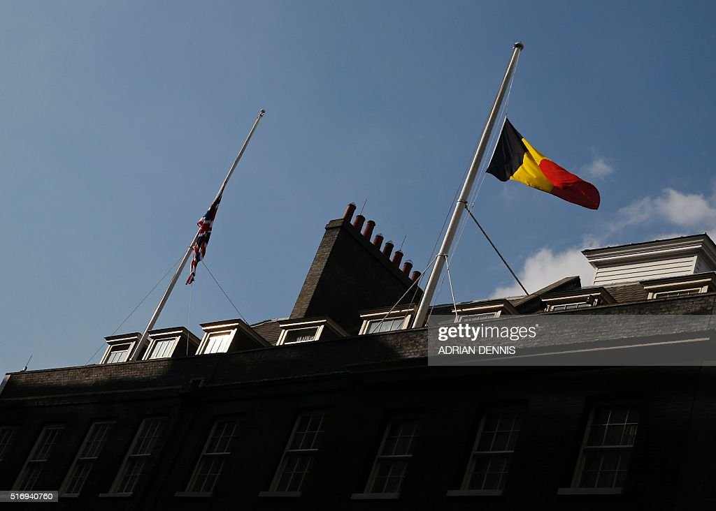 The Union flag and the Belgian flag fly at halfmast above 10 Downing Street in central London on March 22 2016 Britain boosted security at its...