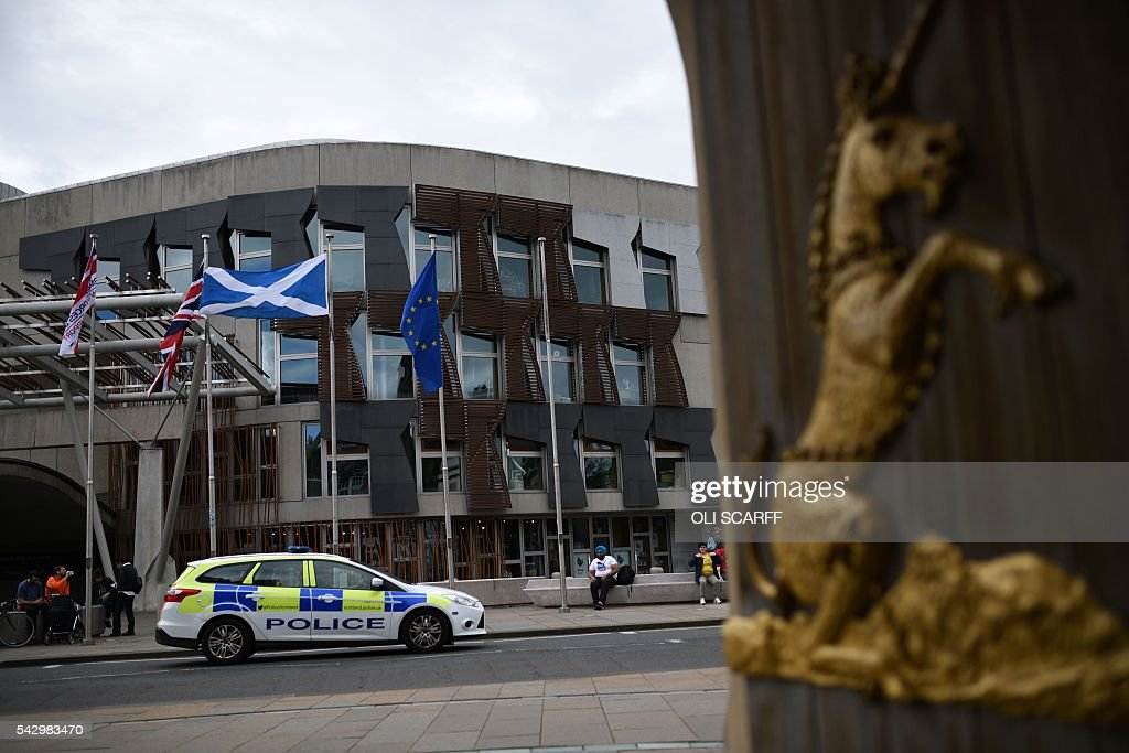 The Union flag, (2L), the Scottish Saltire flag (2R) and the European Union (EU) flag (R) fly outside the Scottish Parliament building in Edinburgh, Scotland on June 25, 2016, following the pro-Brexit result of the UK's EU referendum vote. The result of Britain's June 23 referendum vote to leave the European Union (EU) has pitted parents against children, cities against rural areas, north against south and university graduates against those with fewer qualifications. London, Scotland and Northern Ireland voted to remain in the EU but Wales and large swathes of England, particularly former industrial hubs in the north with many disaffected workers, backed a Brexit. / AFP / OLI